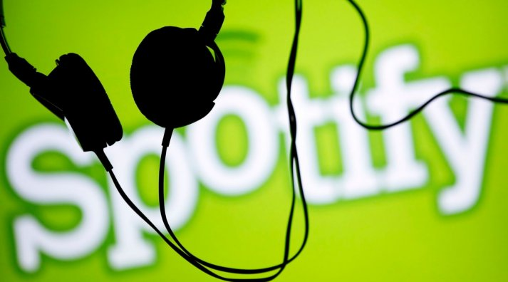 Headsets hang in front of a screen displaying a Spotify logo on it, in Zenica February 20, 2014. Online music streaming service Spotify is recruiting a U.S. financial reporting specialist, adding to speculation that the Swedish start-up is preparing for a share listing, which one banker said could value the firm at as much as $8 billion (4 billion pounds). REUTERS/Dado Ruvic (BOSNIA AND HERZEGOVINA - Tags: SCIENCE TECHNOLOGY BUSINESS SOCIETY)